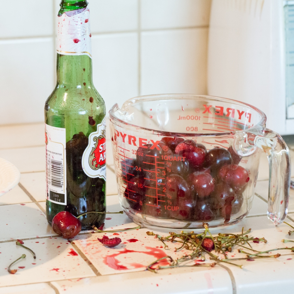 Pitted cherries with the pits in the beer bottle